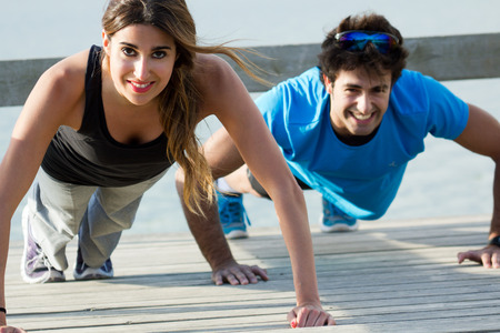 Young couple doing push ups near the sea Stock Photo