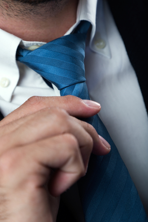 Portrait of businessman without face straightens tie yourself. Isolated on black.