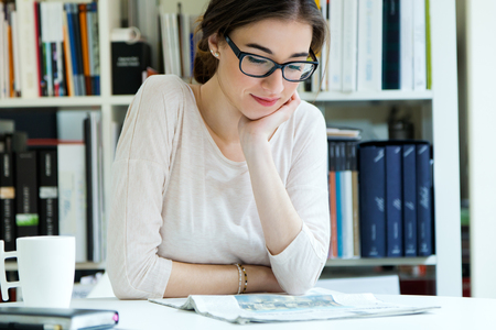 Portrait of young working woman reading the newspaper at office