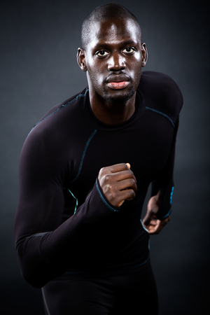 Portrait of athletic man running in black background. Stock Photo