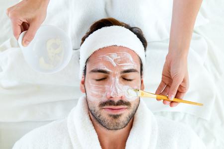 Porträt des Mannes mit Tongesichtsmaske im Schönheitsbad.