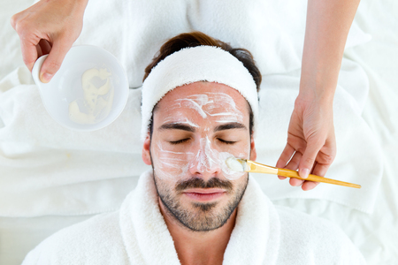Retrato de hombre con mascarilla facial de arcilla en spa de belleza.