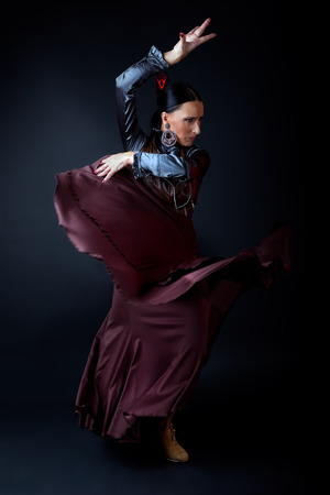 Portrait of young flamenco dancer in beautiful dress on black background.