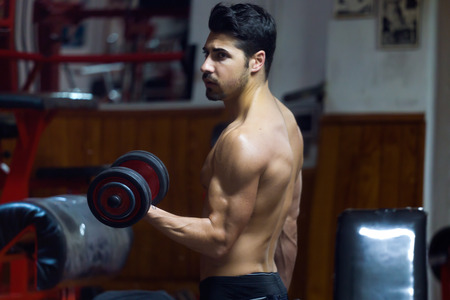 Portrait of young man doing heavy weight exercise in gym.
