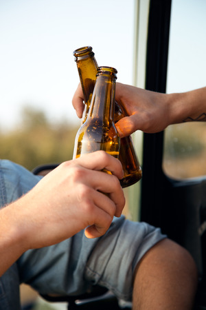 Outdoor portrait of two friends toasting with bottles of beer in car. Reklamní fotografie
