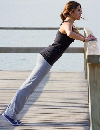 Beautiful young woman doing push ups near the sea