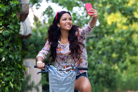 Outdoor portrait of pretty young girl riding bike and taking a selfie.