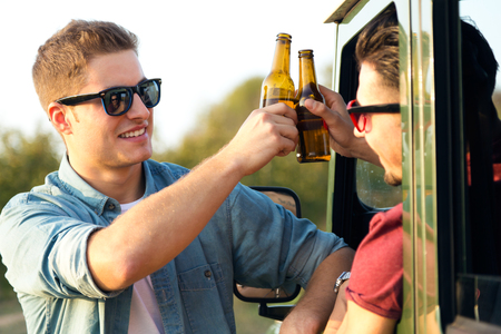 Outdoor portrait of two friends toasting with bottles of beer in car. Reklamní fotografie - 111736578