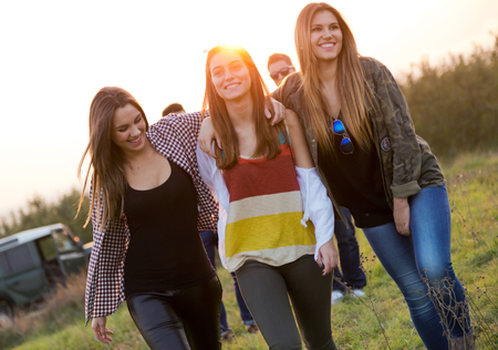 Outdoor portrait of group of friends having fun in field. 写真素材