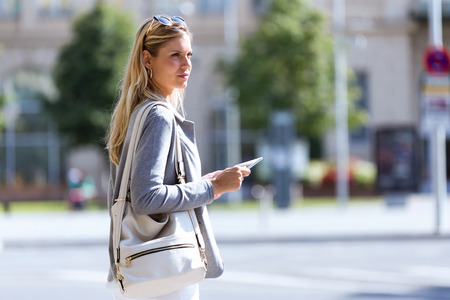 Shot of beautiful young businesswoman working with digital tablet while standing in the street.