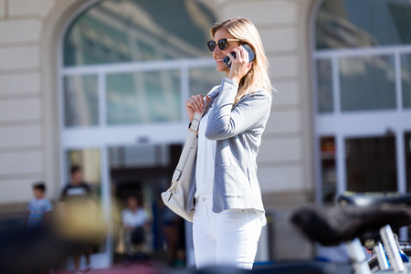 Shot of beautiful young businesswoman talking with her mobile phone while walking in the street. Banco de Imagens