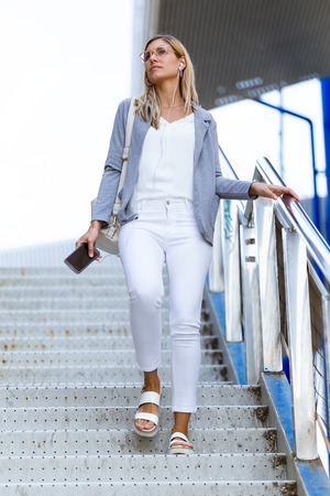 Shot of young beautiful businesswoman walking down stairs and holding her mobile phone near the train station. Banco de Imagens