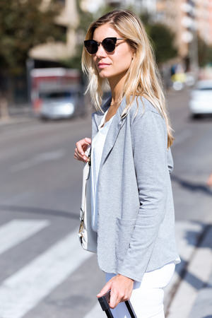 Shot of beautiful young businesswoman looking to sideways while crossing the road with the travel bag. Banco de Imagens