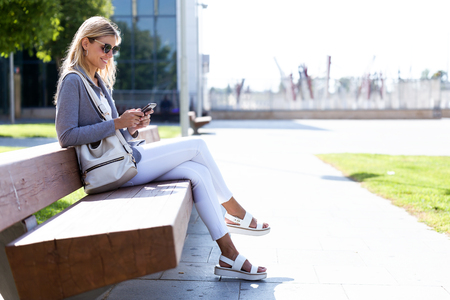 Shot of beautiful young businesswoman texting with her mobile phone while sitting on bank in the street. Banco de Imagens