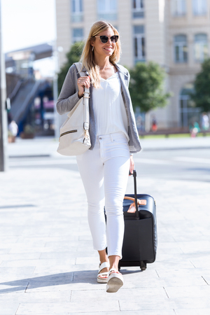 Shot of beautiful young business woman walking with suitcase in the street.