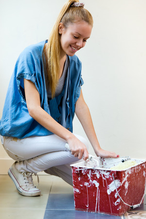 Portrait of young beautiful woman painting her new home. Reklamní fotografie