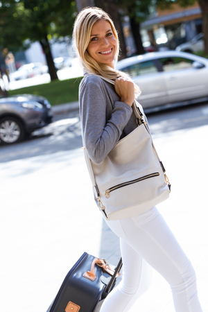Portrait of beautiful young businesswoman looking at camera while walking with suitcase in the street.