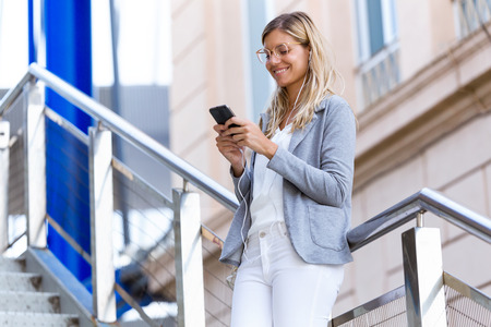 Shot of beautiful young business woman texting with her mobile phone on stairs near train station.