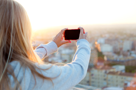 Outdoor portrait of beautiful blonde girl taking pictures of the city. Zdjęcie Seryjne