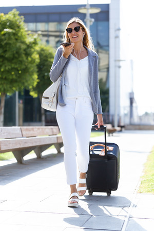 Shot of beautiful young businesswoman talking on the smartphone with hands free while walking with suitcase in the street.