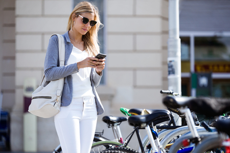 Shot of beautiful young businesswoman texting with her mobile phone while walking in the street. Banco de Imagens