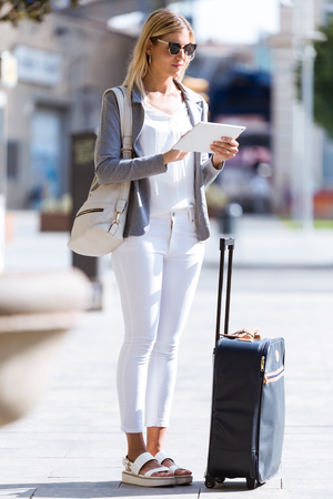 Shot of beautiful young businesswoman working with digital tablet while standing with suitcase in the street.