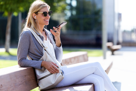 Shot of beautiful young businesswoman talking on the smartphone with hands free while sitting on bank in the street.