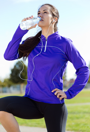 Outdoor portrait of pretty young woman drinking water after running.