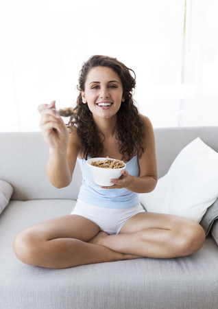 Portrait of beautiful young woman eating cereals at home. Фото со стока