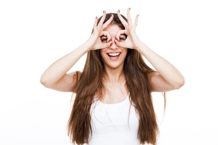 Porträt der schönen jungen Frau, die Fingergläser macht und über weißem Hintergrund lächelt.
