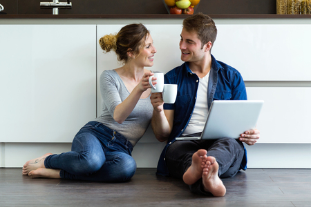 Portrait of beautiful young couple using they digital tablet in the kitchen at home. 写真素材