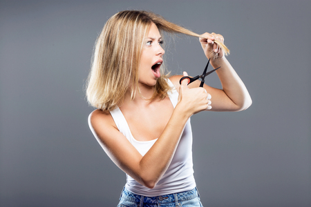 Portrait of beautiful young woman cutting her hair over gray background.