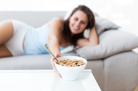 Portrait of beautiful young woman eating cereals at home. Stock Photo
