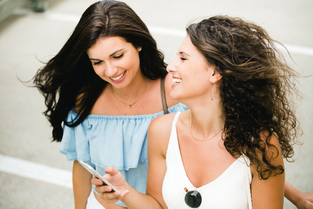 Portrait of beautiful young women having fun with smartphones in the street.