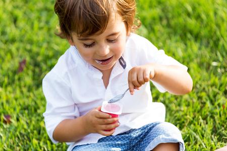 Portret van de kleine jongen die yoghurt eet in het park.