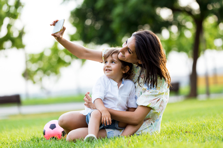 Portrait of beautiful young mother with her son taking a selfie in the park.