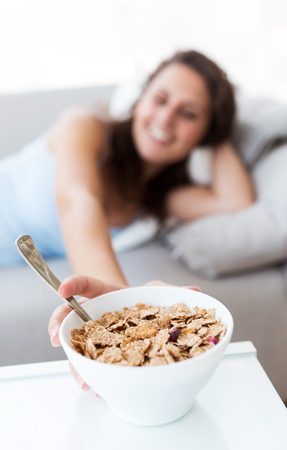 Portrait of beautiful young woman eating cereals at home. Stok Fotoğraf