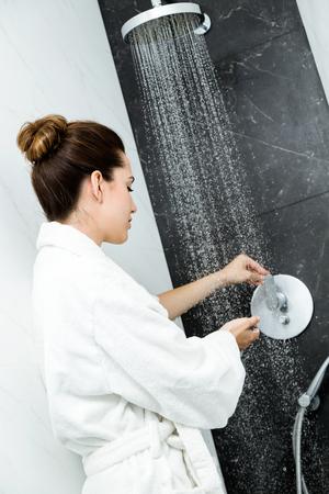 Portrait of womans hands beneath shower of water.