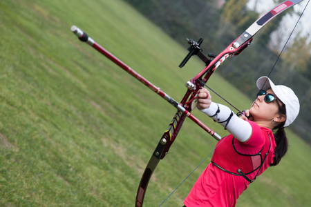 Portrait of female athlete practicing archery in stadium. Stockfoto