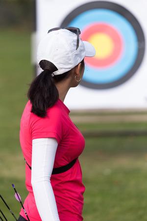 Portrait of female athlete practicing archery in stadium. Stock Photo