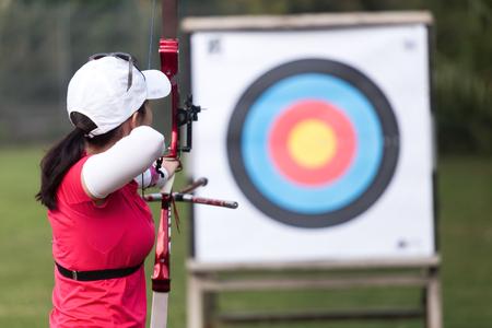 Portrait of female athlete practicing archery in stadium. Reklamní fotografie