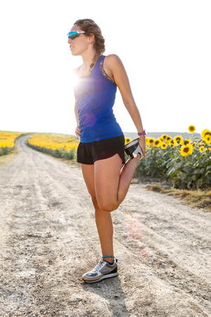 Portrait of beautiful young woman stretching and preparing for running in countryside.