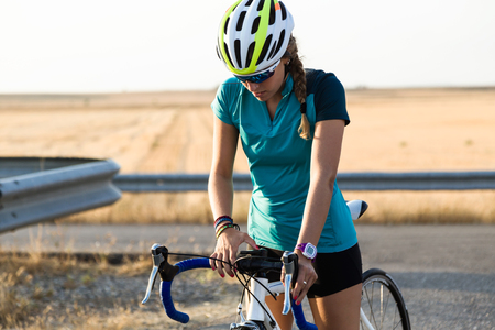 Portrait of beautiful young woman preparing for cycling on road. Stockfoto