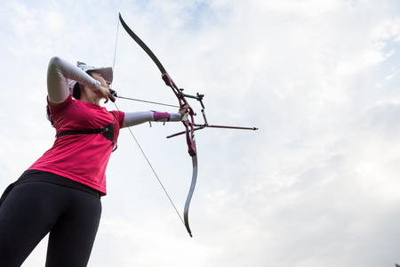 Portrait of female athlete practicing archery in stadium. Stock Photo