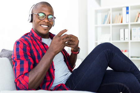 Portrait of handsome young man listening to music with headphones at home.