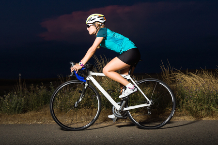 Portrait of beautiful young woman cycling on the road.