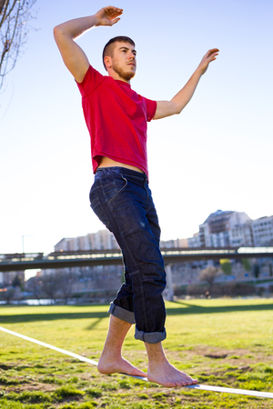 Portrait of handsome young man walking on slackline in the park. Stock Photo