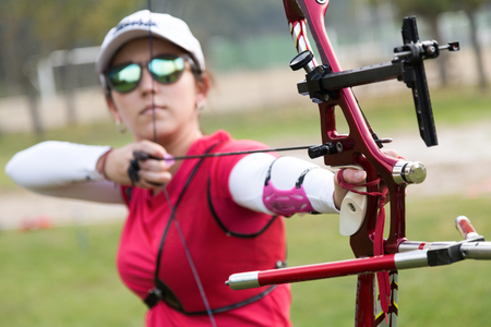 Portrait of female athlete practicing archery in stadium. 스톡 콘텐츠