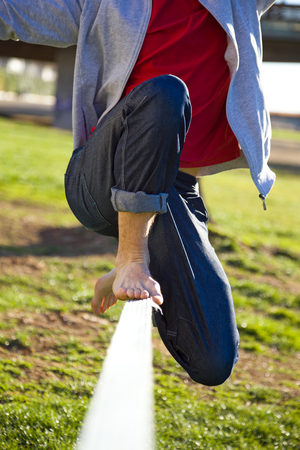 Detail of the legs of a man walking on slackline in the park.