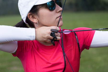 Portrait of female athlete practicing archery in stadium. 版權商用圖片